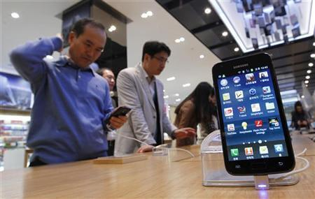 Customers look at Samsung Electronics' Galaxy S II LTE smartphones on display at a shop in Seoul