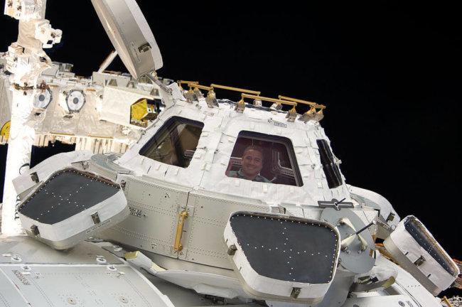 1024px-STS-130_George_Zamka_looks_through_the_Cupola