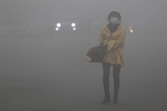 A woman wearing a face mask walks in heavy smog in Haerbin, northeast China's Heilongjiang province, on Oktober 23, 2013. Clouds of pollution blanketed Haerbin, cutting visibility to 10 metres (33 feet). (Photo by AFP Photo)